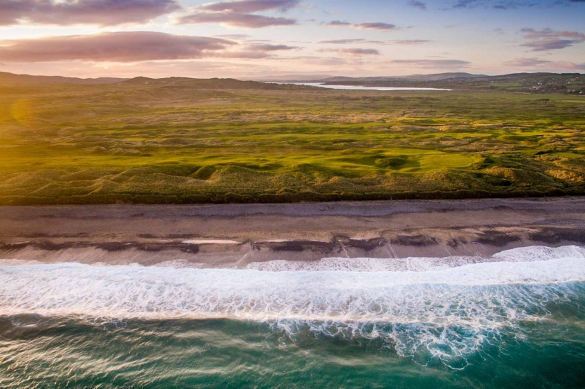 An aerial photo of the Ballyliffin Golf Club Glashedy Golf Course and the crashing waves of the Atlantic.