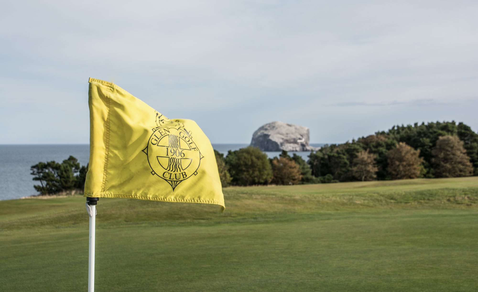 A flag blowing in the wind at Glen Golf Club East Links.