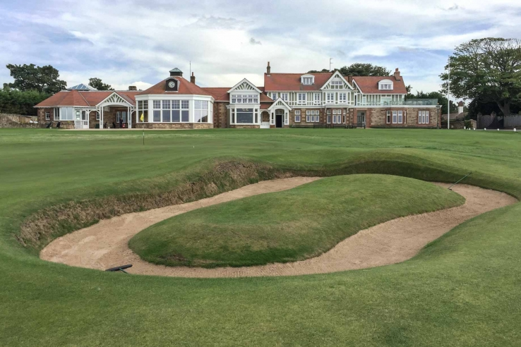 18th green at Muirfield with clubhouse and Simpson island bunker visible.