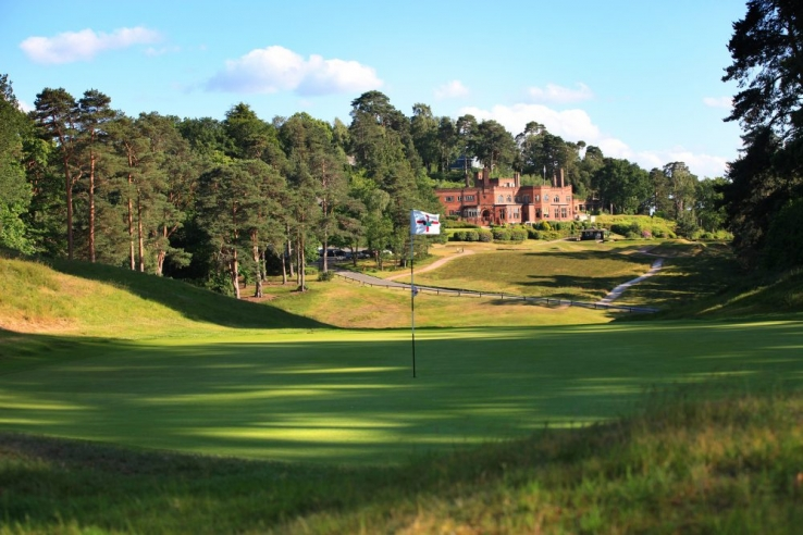 The 1st green with the iconic brick clubhouse at St Georges Hill Golf Club.