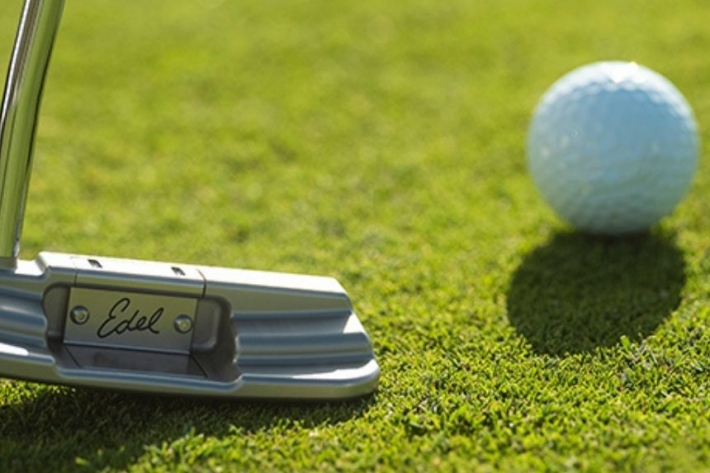 A photo of one of Edel Golf's Custom Putters, the Edel EAS 1.0 Blade Putter, on a green.